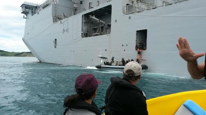 Gestrande toeristen gaan het marineschip op.