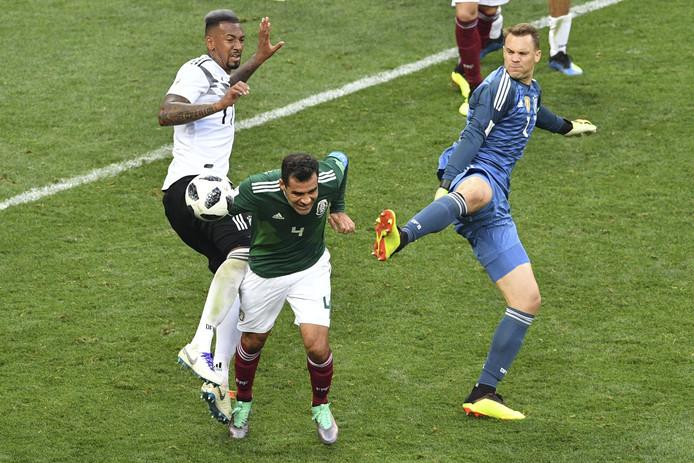 Opmerkelijk beeld in de slotfase van Duitsland-Mexico: Rafael Marquez (midden) kopt de bal weg als de Duitsers Jerome Boateng (links) en doelman Manuel Neuer zich bij een corner van de wereldkampioen in het zestienmetergebied van Mexico hebben gemeld.
