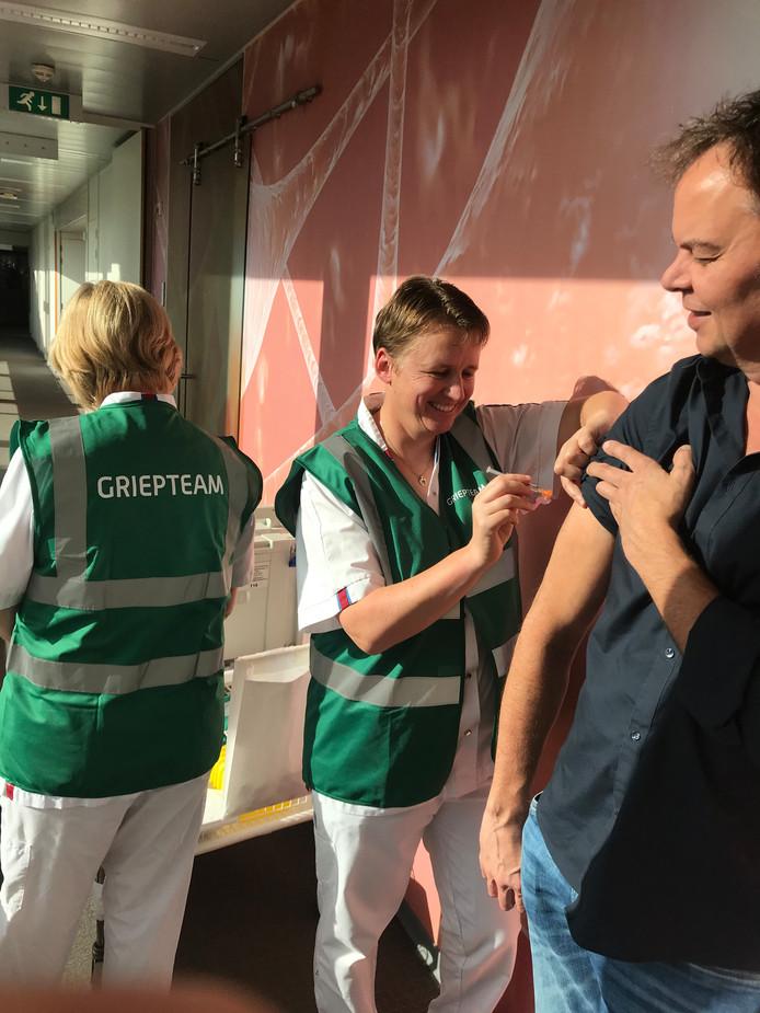 René Maas van ZorgSaam krijgt de griepprik van Sandra Knol van het griepteam.