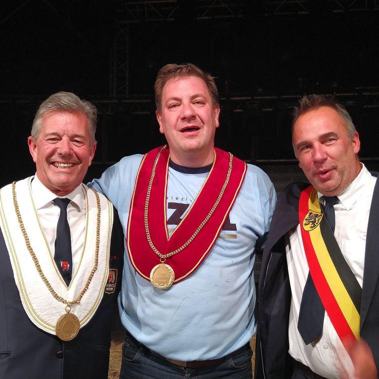 David, de nieuwe Koning Ezel, tussen Eddy Lafaut van de Orde van de Ezel en Francis Benoit, burgemeester