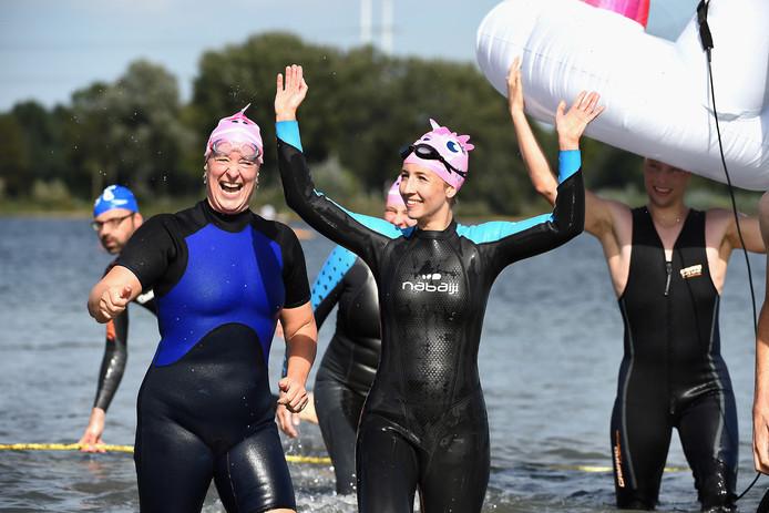 Deelnemers bij de finish van Swim to Fight Cancer op Stroombroek bij Braamt komen tevreden het water uit.