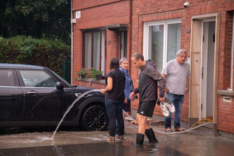 Bewoners pompen het water uit hun huis.