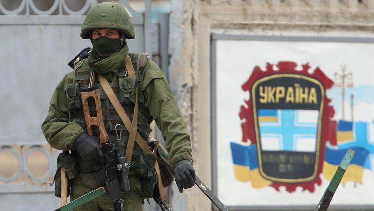 Een vermoedelijk Russische soldaat (zonder insignes) voor een Oekraïense legerbasis op de Krim. Beeld getty