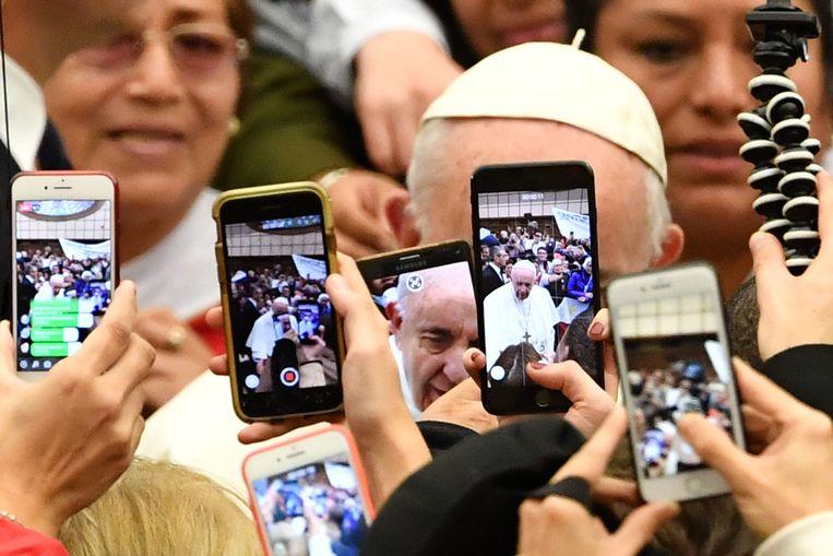Gelovige toeschouwers maken foto's van paus Franciscus in het Vaticaan, 6 januari 2019. Beeld AFP