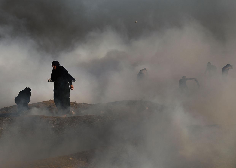 Twee vrouwen in een wolk van traangas nabij de grens tussen Gaza en Israël.