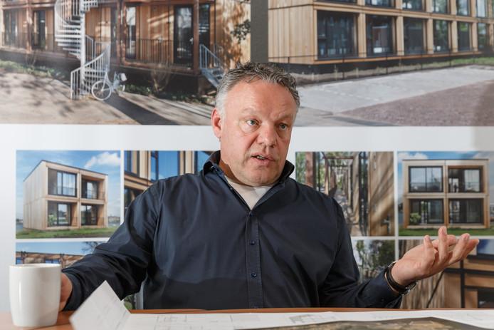 Gerrit Jansen met achter hem panelen waarop de woningen die aan de Scholtensteeg komen afgebeeld staan.