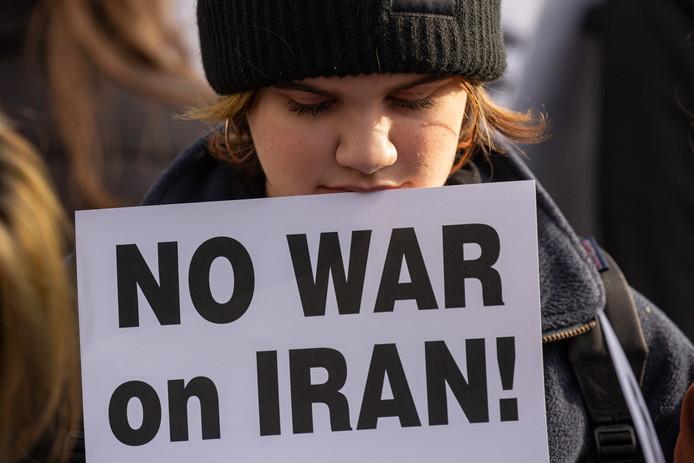 Een demonstrant in Seattle draagt een bordje met daarop 'Geen oorlog in Iran!'
