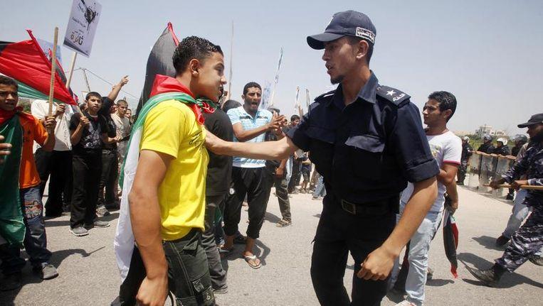 Een demonstrant wordt tegengehouden door een Palestijnse politieagent Beeld reuters