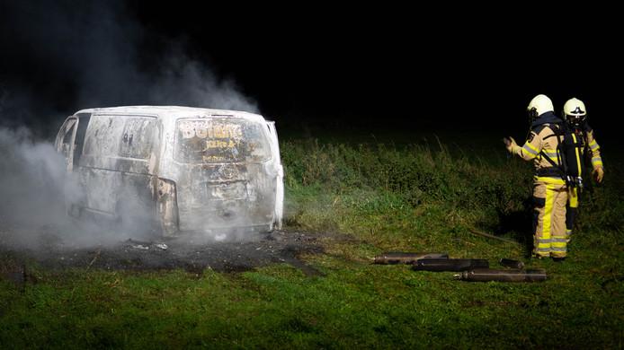 Het uitgebrande busje met op de voorgrond de drie gasflessen.