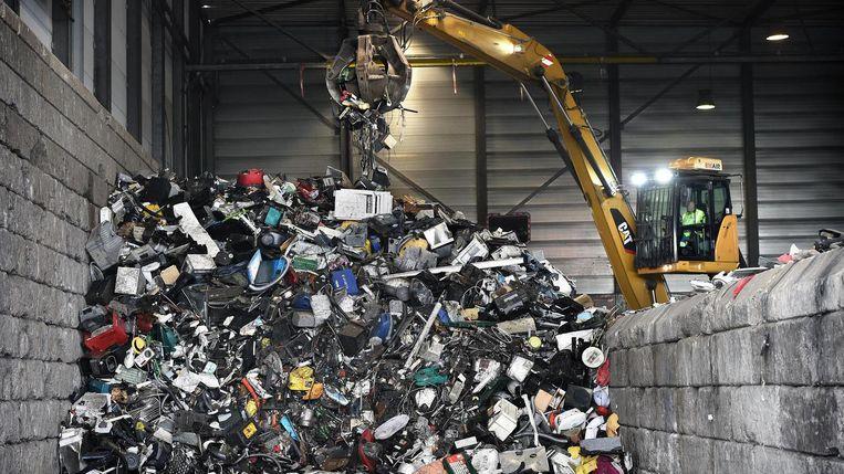 Een kraan van Sims Recycling Solutions in Eindhoven pakt afval op om het vervolgens op een lopende band te leggen Beeld Marcel van den Bergh
