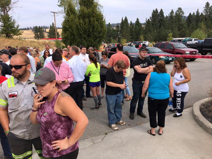 Ouders verzamelen zich op de parkeerplaats bij de school om te wachten op hun kinderen.