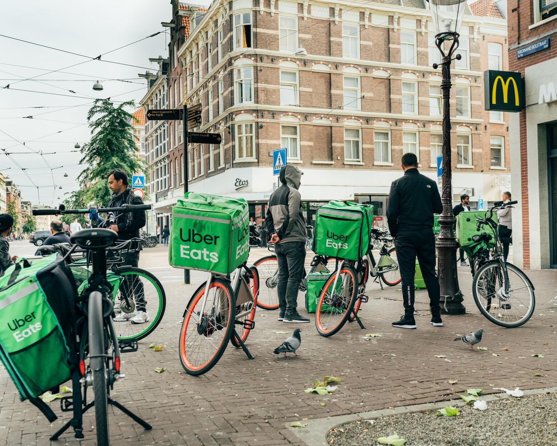 Bezorgers van Uber Eats hebben een tekort aan werk en verzamelen bij de McDonald's in de Pijp, Amsterdam, om werk te krijgen.  Beeld Rebecca Fertinel