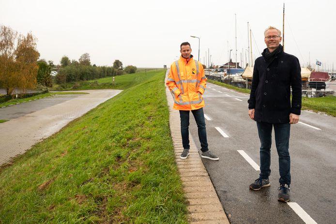 Projectleiders Kevin van den Borne (links) en Erwin Klerkx op de Westdijk in Bunschoten-Spakenburg. De vervuilde grond ligt tegen de linkerzijde van de dijk aan.