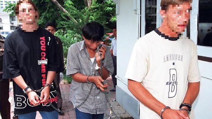 Machiel Kuijt (r) wordt geboeid weggevoerd na zijn arrestatie in Bangkok wegens vermeende drugshandel op 17 april 1997.