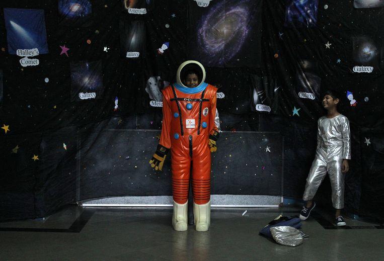Het Indian Space Research Organisation heeft in het Indiaase Mumbai een expositie ingericht over ruimtevaarttechnologie. Schoolkinderen mochten daar gisteren tot hun grote vreugde zich in een ruimtevaartpak hijsen.  foto reuters Beeld Reuters