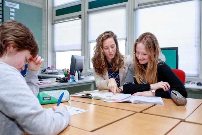 Docent Marieke van Hoof (links) helpt Roos  en Shana (op de voorgrond) hoe zij weer kunnen leren om te leren.