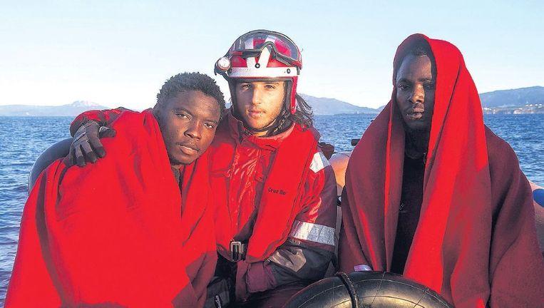 Een medewerker van het Rode Kruis poseert met twee mannen die uit een bootje zijn gered voor de kust van Zuid-Spanje. Beeld afp