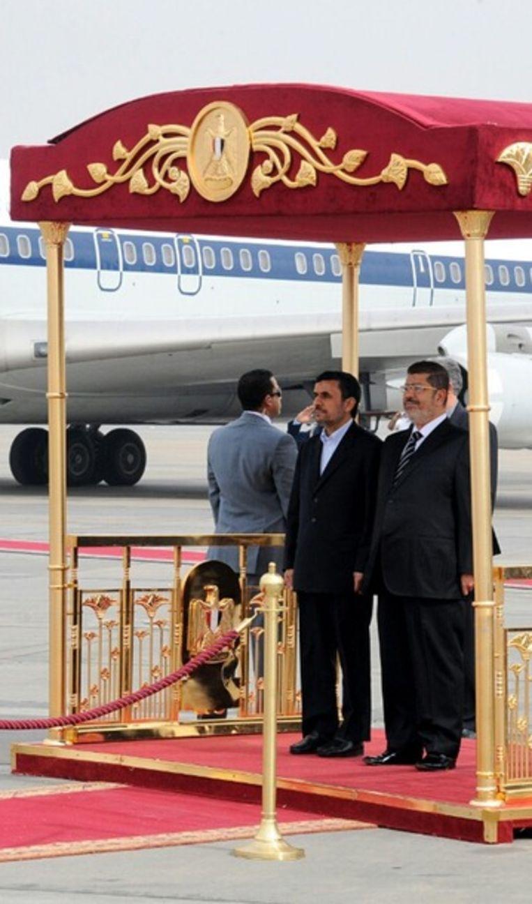 Morsi en Ahmadinejad tijdens de ontvangstceremonie op het vliegveld van Caïro. Beeld ANP