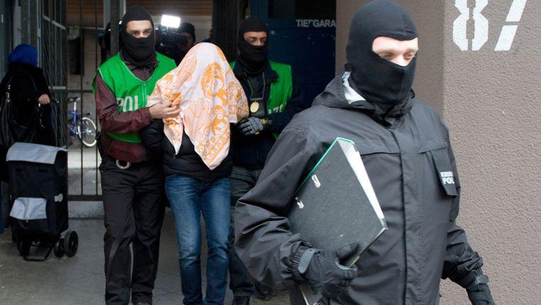 Agenten nemen een verdachte mee na een inval in zijn huis. De politie heeft in verschillende panden invallen gedaan, om mensen die verdacht worden van banden met Islamitische Staat op te pakken. Beeld ap