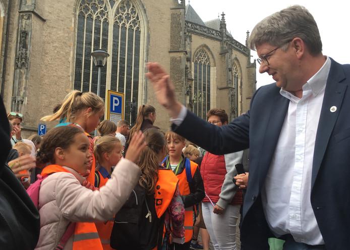 Raadslid Erik Stegink van Gemeentebelang onthaalt de kinderen bij de intocht van de Deventer vierdaagse met een high-five.