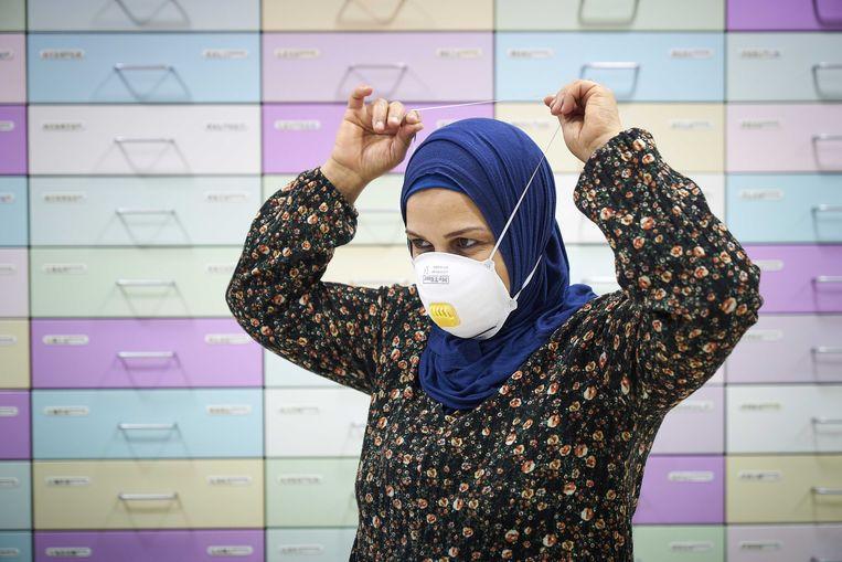 Een werknemer van een apotheek demonstreert hoe je een mondkapje opzet. Nu er meer gevallen van het coronavirus in Europa worden vastgesteld, dreigt er een tekort aan onder andere mondkapjes in Nederland.  Beeld ANP