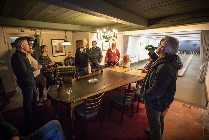Een groep belangstellenden laat zich bij de kegelbanen in het JW Racerhuis voorlichten door Willy Brons.