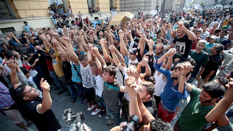 Syrische en Afghaanse vluchtelingen protesteren voor het Keletistation in Boedapest. Beeld afp