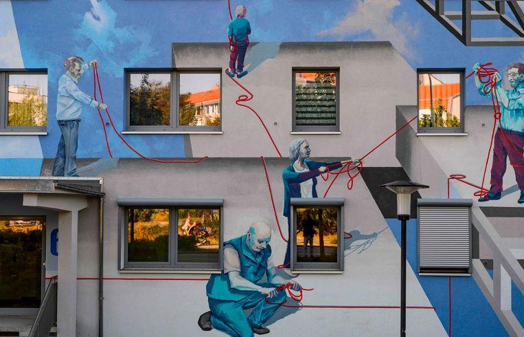 Een klassieke Oost-Duitse 'Plattenbau'- woonkazerne in de stad Halle is opgefleurd door het kunstenaarscollectief 'Freiraumgalerie'. Het schilderproject is bedoeld om de sociale cohesie in de wijk te vergroten.  Beeld AFP