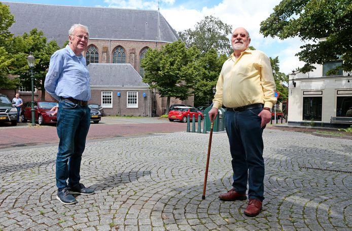 Cees van Zelderen (rechts) en Leendert Spijker zijn bang dat nieuwbouw op de plek van het witte huisje rechts hoger wordt dan de nok van het kerkdak.