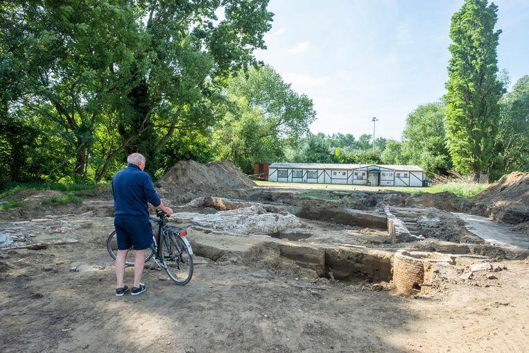 Een fietser bekijkt de opgravingen in Park Groot Schijn.