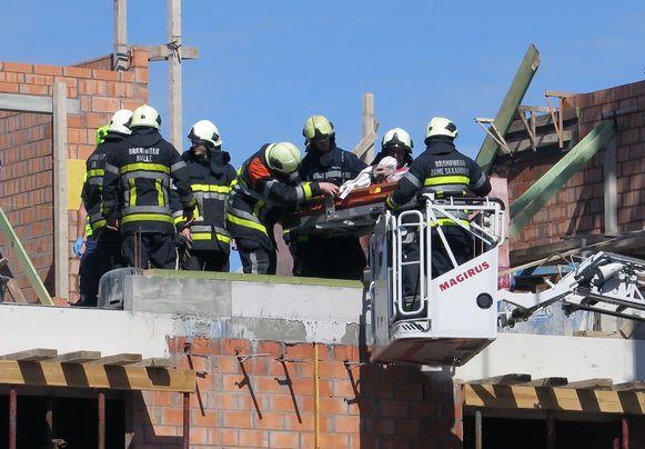 Brandweerlui halen het slachtoffer met een ladderwagen naar beneden.