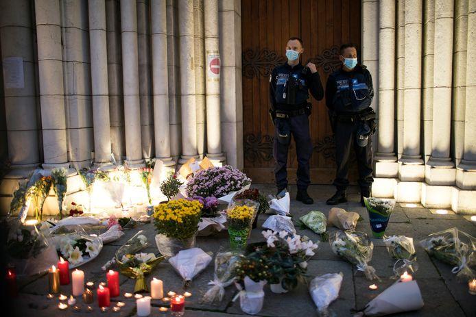 Franse agenten bewaken de ingang van de Onze Lieve Vrouw basiliek in Nice, waar mensen bloemen en kaarsjes hebben achtergelaten ter nagedachtenis aan de drie doden.