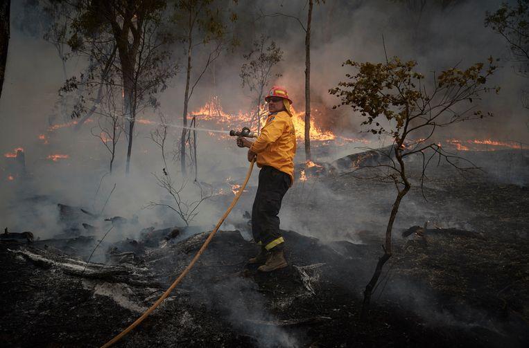 Een brandweerman bestrijdt het vuur in de Zuid-Australische Snowy Mountains. Beeld Hollandse Hoogte / Polaris Images