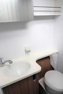 Wasbak en toilet in de badkamer, waarvan de ruimte flexibel is dankzij een lamellendeur die verschillende posities kan innemen