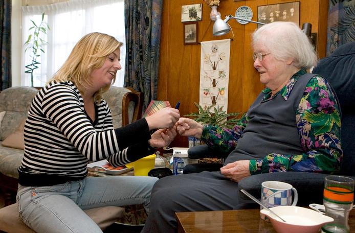 Een wijkverpleegkundige controleert de suikerspiegel bij een mevrouw met suikerziekte en hartfalen.