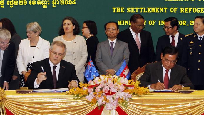 De Australische minister van Immigratie Scott Morrison (links) tekent in Cambodja een akkoord voor de opvang van immigranten.