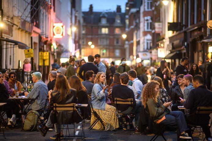 Mensen zitten op terrasjes in Soho, Londen.