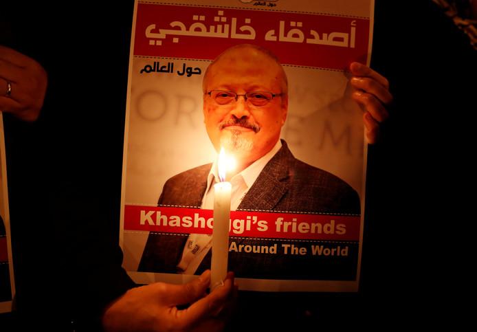 Een demonstrante met een foto van Jamal Khashoggi voor het Saoedische consulaat vorige maand.