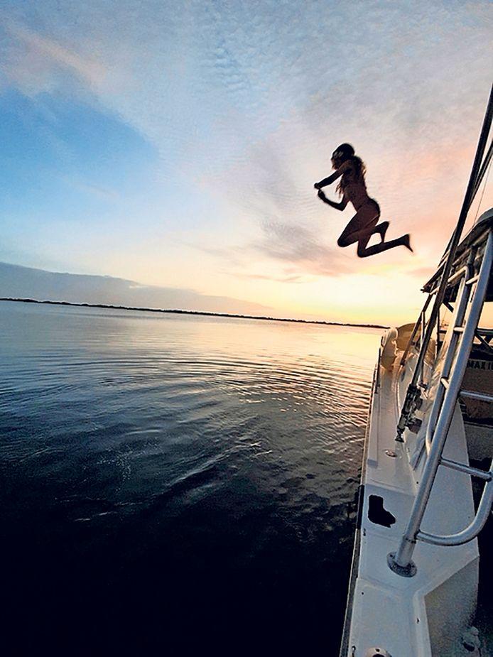 Een andere weekwinnaar van de zomerfotowedstrijd. Vakantie in Curaçao kan weer. Madelief Splinter sprong tijdens een boottocht bij de ondergaande zon vanaf de boot de Fuikbaai in, en vader Ed Splinter uit Waalwijk legde het vast.