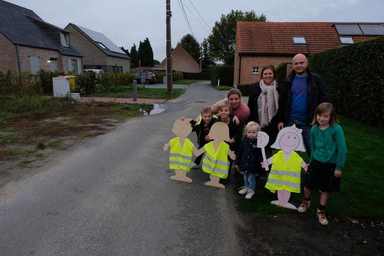 De buurtbewoners met enkele van hun zelfgeknutselde 'kinderborden'.