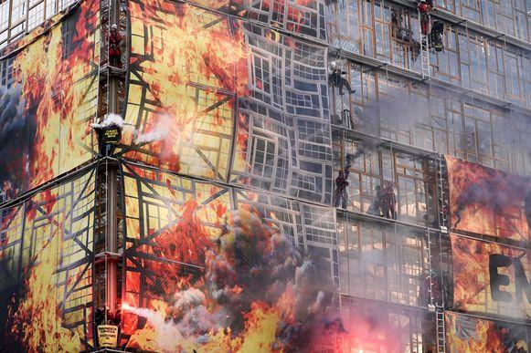 De actievoerders steken Bengaals vuur af aan hun vlammen-banner waardoor het lijkt alsof het gebouw in brand staat.