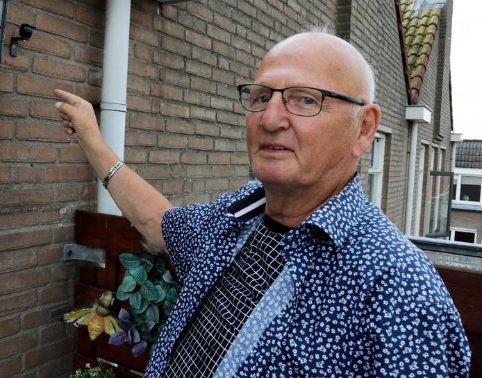 Jan Smits wijst het kleine apparaatje aan dat is bevestigd aan de buitenmuur van zijn huis.
