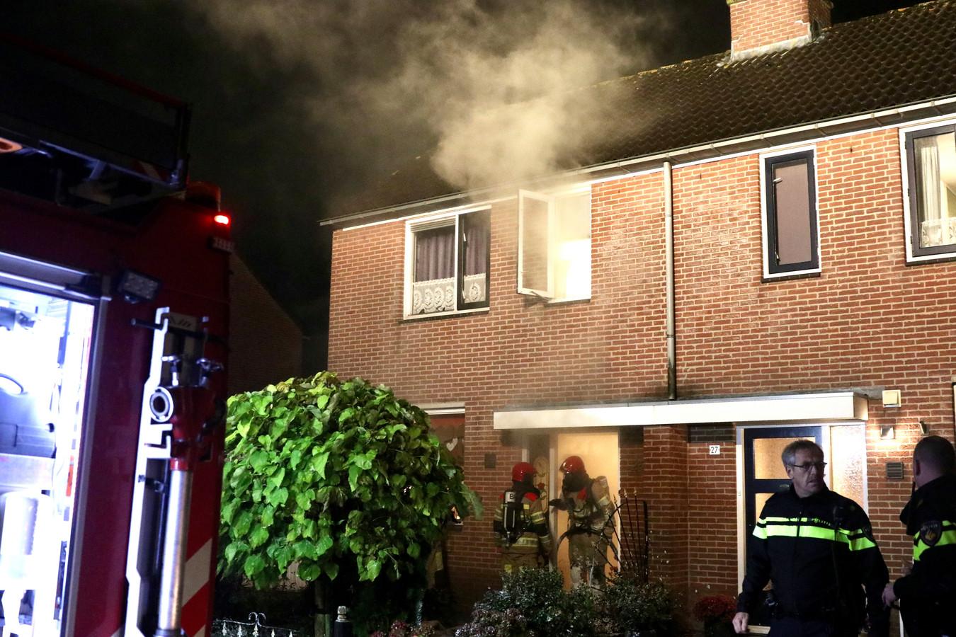 Brandweer bij de woning in Emmeloord, waar de rook uit het raam komt.