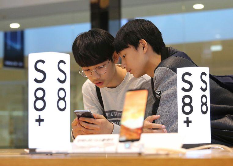 Jonge Zuid-Koreanen bekijken een Samsung Electronics Galaxy S8 Plus-smartphone in een winkel in hoofdstad Seoel.