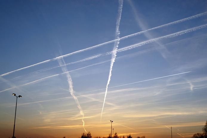 Strepen in de lucht van een vliegtuig bij ondergaande zon op 21 maart 2009.