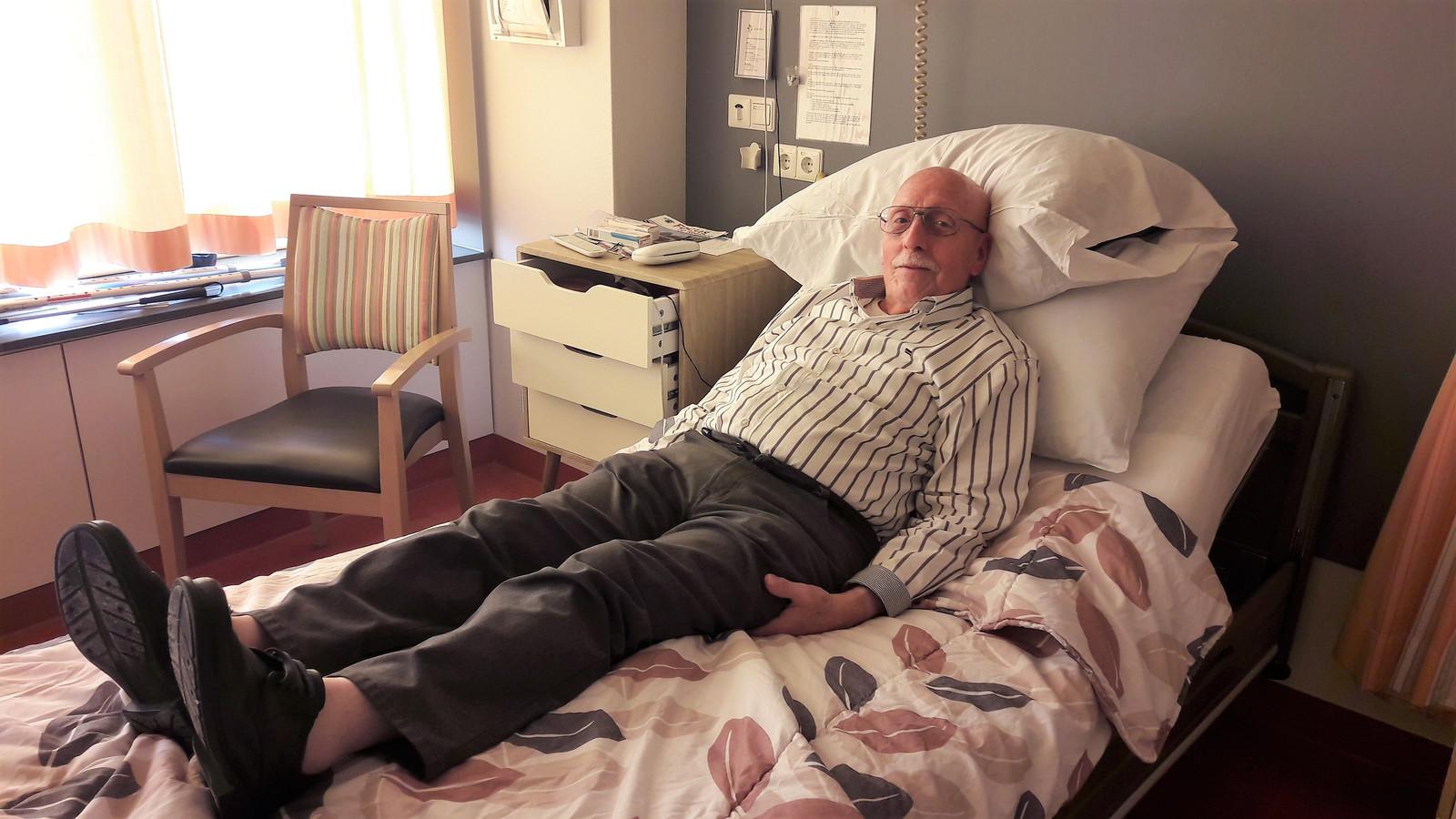 Jan Essens uit Tilburg  rust na de therapie uit op bed.