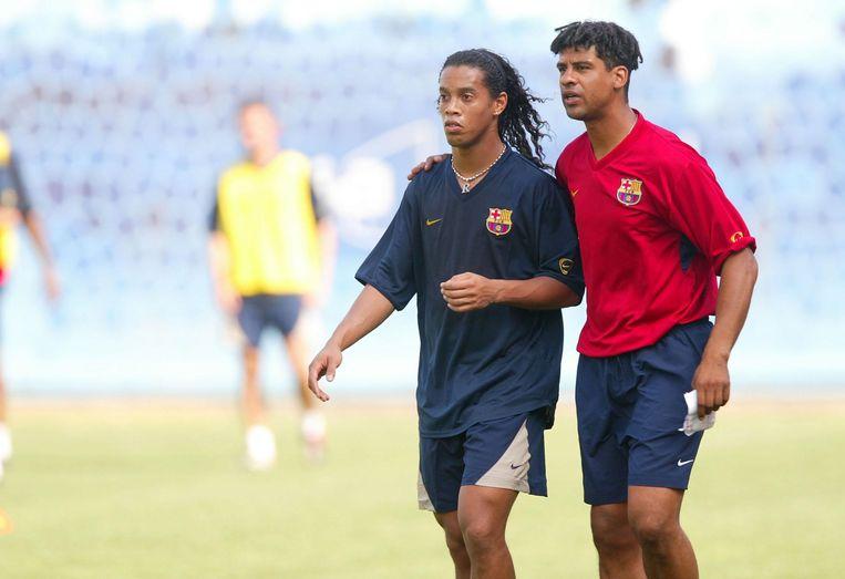 Rijkaard in zijn tijd bij FC Barcelona met toenmalig sterspeler Ronaldinho.  Beeld BSR