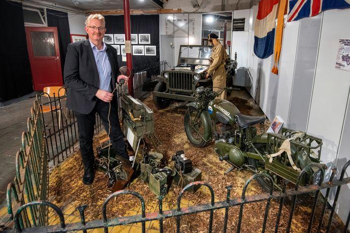 Conservator Jean Kreunen bij een motor, een jeep en een radioinstallatie in het tijdelijke oorlogsmuseum in Velp.