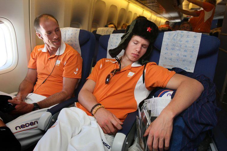 Diederik Simon kijkt naar een slapende Jozef Klaasen op de weg terug van de Spelen in Peking. afloop van de 29e Olympische Spelen maandag. Beeld ANP