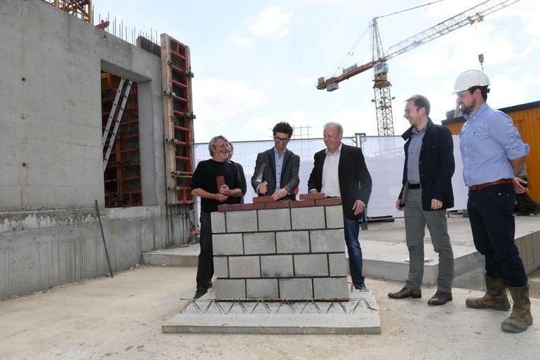 Schepen van Vastgoed Mohamed Ridouani (tweede van links) legt de eerste steen van het project.